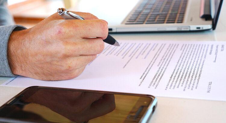 Hand mit Stift über einem Schriftstück